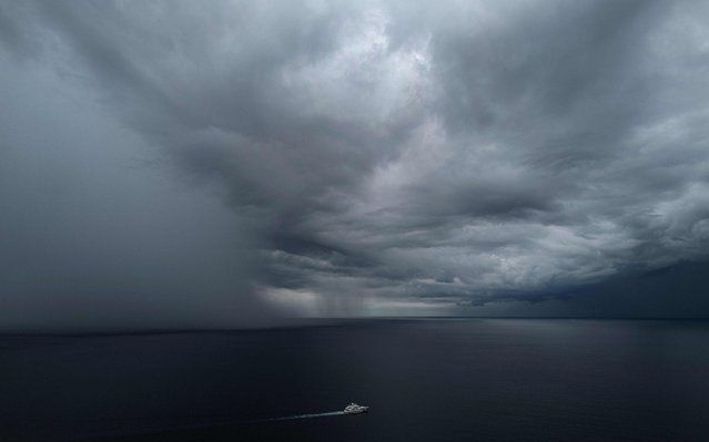 A yacht sails ahead of an approaching rainstorm over The Mediterranean Sea, near the coast of the French Riviera city of Nice, southern France on September 22, 2020. (Photo by Valery Hache/AFP Photo)