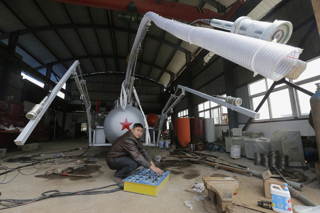 Zhang Wuyi looks up as he squats under a suction pipe of his new submarine that captures sea cucumbers at his workshop in Wuhan, Hubei province, March 25, 2013. Zhang, a 38-year-old local farmer who is interested in scientific inventions, has independently made eight miniature submarines with several fellow engineers, one of which was sold to a businessman in Dalian at a price of 100,000 yuan ($15,855) in 2011. The submarines, mainly designed for harvesting aquatic products, such as sea cucumber, have a diving depth of 20-30 metres (66-98 feet), and can travel for 10 hours, local media reported. (Photo by Reuters/Stringer)