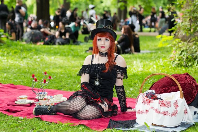 A girl sits on a red blanket on the lawn during the traditional park picnic on the first day of the annual Wave-Gotik Treffen, or Wave and Goth Festival, on May 17, 2013 in Leipzig, Germany. The four-day festival, in which elaborate fashion is a must, brings together over 20,000 Wave, Goth and steam punk enthusiasts from all over the world for concerts, readings, films, a Middle Ages market and workshops. (Photo by Marco Prosch)