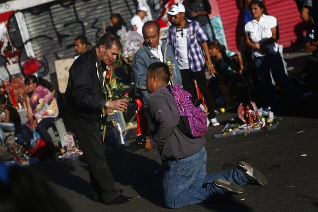 A follower kneels down while a man pours an alcoholic beverage over a figure of La Santa Muerte (The Saint of Death), a cult figure often depicted as a skeletal grim reaper, at Tepito neighbourhood in Mexico City January 1, 2015. (Photo by Edgard Garrido/Reuters)