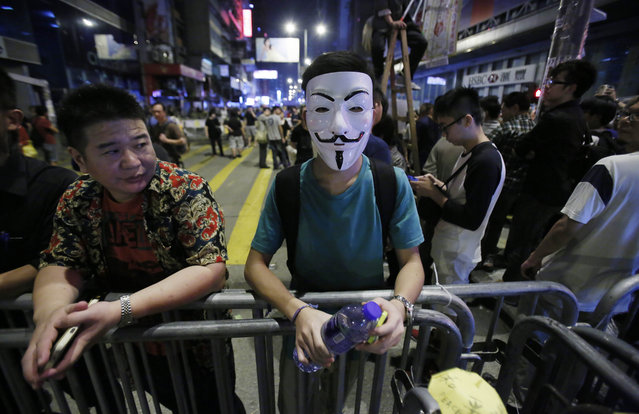 Hong Kong: A pro-democracy protester wears the Guy Fawkes mask at a barricade in the occupied area in the Mong Kok district of Hong Kong, early Tuesday, October 21, 2014. (Photo by Wally Santana/AP Photo)