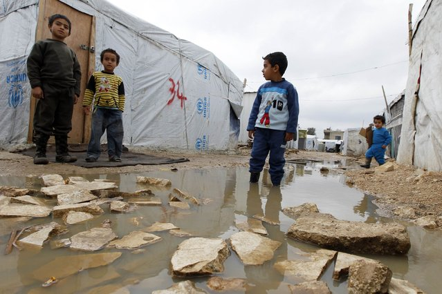 A Syrian refugee boy stands in a pool of water as he looks at others outside tents at a makeshift settlement in Bar Elias in the Bekaa valley January 5, 2015. (Photo by Mohamed Azakir/Reuters)