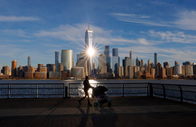 The sun reflects off the windows of One World Trade Center in New York City as a woman walks on a pier on December 27, 2020 in Jersey City, New Jersey. (Photo by Gary Hershorn/Getty Images)