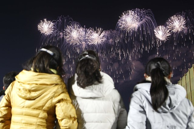 A fireworks display decorates the night sky to celebrate the New Year, as crowds of people look on, at Kim Il Sung Square in Pyongyang, North Korea, early Friday, January 1, 2021. (Photo by Jon Chol Jin/AP Photo)