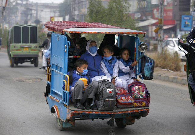 Students wearing face masks to protect against the coronavirus, ride in a tri-wheeler to school in Lahore, Pakistan, Wednesday, November 25, 2020. Pakistan will again close all educational institutions as of Thursday November 26, 2020, because of a steady and increasingly drastic increase in coronavirus cases. (Photo by K.M.Chaudary/AP Photo)