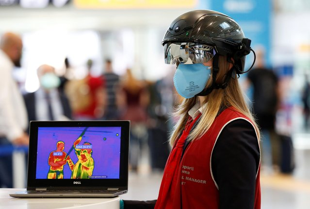 """An airport official wears a """"Smart Helmet"""", a portable thermoscanner that can measure the temperature of passengers at a distance, at the Fiumicino airport, after Italy begun a gradual end to a nationwide lockdown due to the coronavirus disease (COVID-19), in Rome, Italy on May 6, 2020. (Photo by Remo Casilli/Reuters)"""