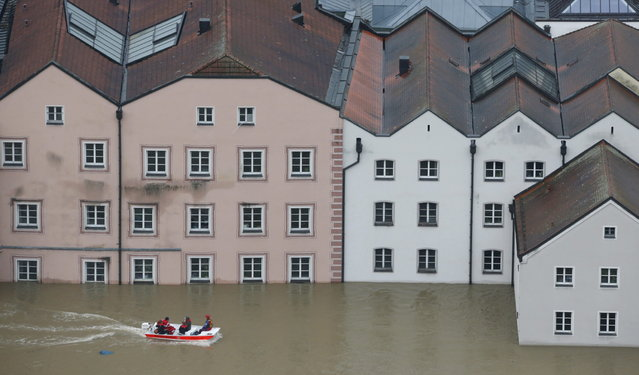 "Members of the Red Cross make their way by boats in the flooded street in the center of Passau, southern Germany, Monday, June 3, 2013. Raging waters from three rivers have flooded large parts of the southeast German city following days of heavy rainfall in central Europe. A spokesman for the city's crisis center said Monday that the situation was ""extremely dramatic"" and waters are expected to rise further by midday to their level highest in 70 years. (Photo by Matthias Schrader/AP Photo)"