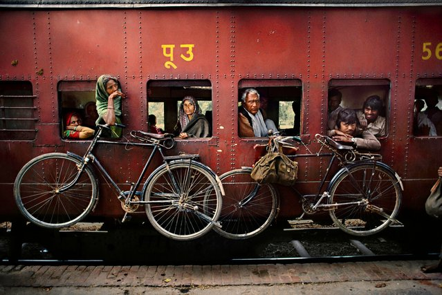 Bicycles hanging from the side of a train, West Bengal, 1983. (Photo by Steve McCurry)