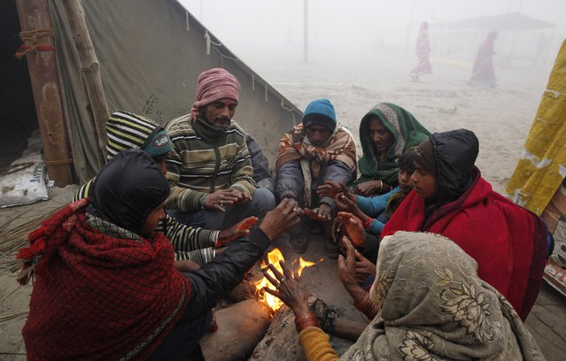 "Hindu devotees warm themselves around a bonfire on a cold foggy morning after bathing in the Sangam, the confluence of rivers Ganges and Yamuna, on Makar Sankranti festival during the annual traditional fair of ""Magh Mela"" in Allahabad, India, Wednesday, January 14, 2015. (Photo by Rajesh Kumar Singh/AP Photo)"