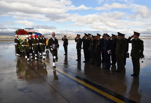 A picture released and taken on November 30, 2015 by Turkish army press office shows Turkish soldiers walking by officials of Russian army as they carry the coffin of Russian pilot Lt. Col. Oleg Peshkov into a Russian Air Force transport during a ceremony at Esenboga Airport in Ankara. Turkey sent back to Russia the body of a pilot killed when his plane was shot down by the Turkish air force for allegedly violating its air space on the Syrian border. (Photo by AFP Photo/Turkish Army Press Office)
