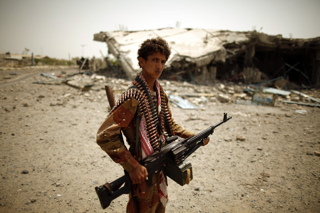 An army soldier stands near a building destroyed during recent fighting between the army and al Qaeda-linked militants in the southern Yemeni city of Zinjibar June 21, 2012. (Photo by Khaled Abdullah/Reuters)