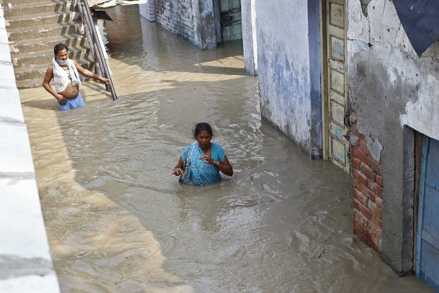 Residents wade through an alley flooded with the rising water level of river Yamuna after heavy monsoon rains in New Delhi June 19, 2013. The rains are at least twice as heavy as usual in northwest and central India as the June-September monsoon spreads north, covering the whole country a month faster than normal. (Photo by Anindito Mukherjee/Reuters)