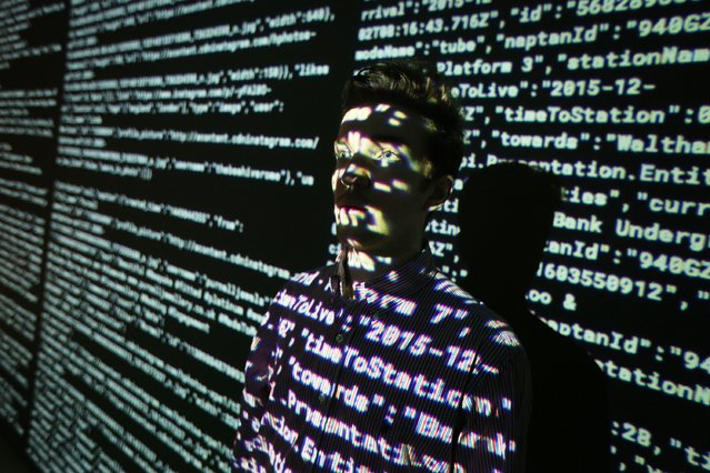 A staff member stands in a projection of live data feeds from (L-R) Twitter, Instagram and Transport for London at the Big Bang Data exhibition at Somerset House on December 2, 2015 in London, England. (Photo by Peter Macdiarmid/Getty Images for Somerset House)