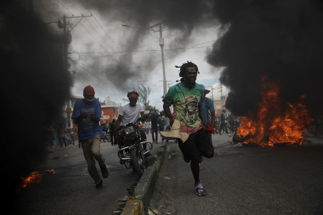 Protestors run past burning tires during a march demanding the resignation of Haiti's President Jovenel Moise, at the 217th anniversary of the Battle of Vertieres, the last major battle of Haitian independence from France, in Port-au-Prince, Haiti, November 18, 2020. (Photo by Andres Martinez Casares/Reuters)