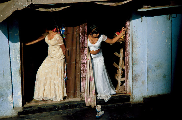 Prostitutes, who are known as cage girls and are often s*x slaves, display themselves on a Mumbai street, 2002. (Photo by Jodi Cobb/National Geographic)
