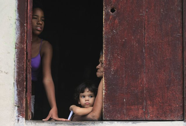 A girl looks out of a window next to an elderly woman holding a child in downtown Havana January 20, 2015. (Photo by Reuters/Stringer)
