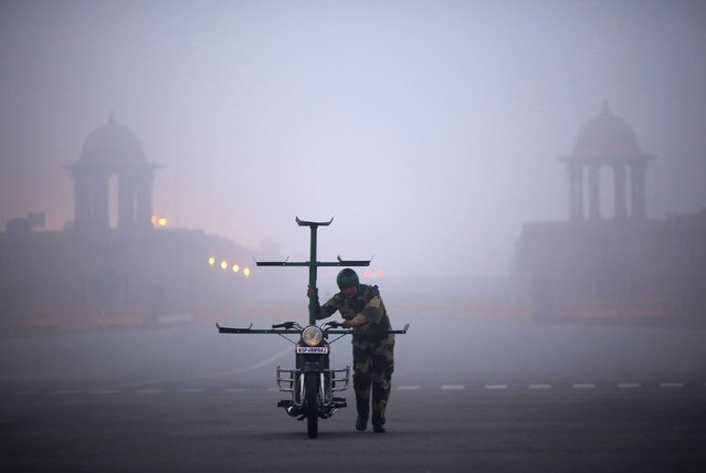 """An India's Border Security Force (BSF) """"Daredevils"""" motorcycle rider arrives to perform during the rehearsal for the Republic Day parade on a foggy winter morning in New Delhi January 16, 2015. (Photo by Ahmad Masood/Reuters)"""