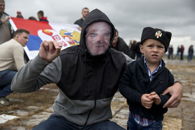 A Serb man with a child wears a face mask depicting Serbian war criminal Ratko Mladic as he participates in a ceremony commemorating a medieval battle with invading Ottoman forces in 1389 at Gazimestan, Kosovo, Thursday, June 28, 2018. Hundreds of Serbs gathered on Thursday to mark the 629th anniversary of the battle where the Serbian army was defeated by the Ottoman Empire. (Photo by Visar Kryeziu/AP Photo)