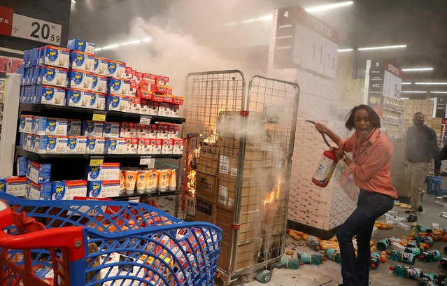 A woman puts out a fire at a vandalized Carrefour store during a march in Sao Paulo, Brazil on National Black Consciousness Day and in protest against the death of Joao Alberto Silveira Freitas, November 20, 2020. Protests were sparked across Brazil after security guards beat Joao Alberto Silveira Freitas, a 40-year-old Black man, to death at a Carrefour Brasil supermarket in the southern Brazilian city of Porto Alegre. (Photo by Amanda Perobelli/Reuters)