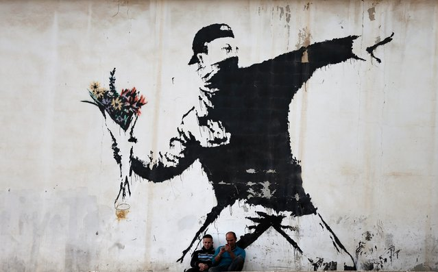 Two men are sitting in front of a famous graffiti of British street artist Banksy, painted on a wall of a gas station in the West Bank city of Bethlehem on December 16, 2015. (Photo by Thomas Coex/AFP Photo)