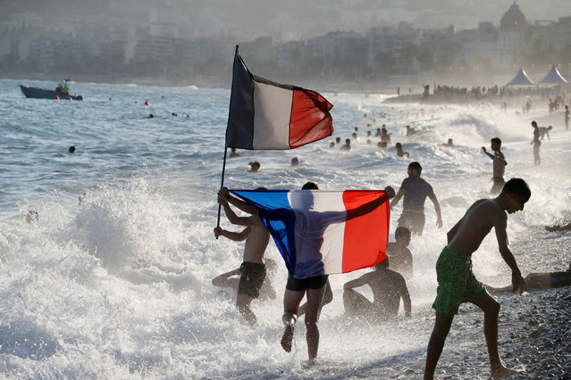 People wave a French flag and celebrate as they swim in the sea after France won the Russia 2018 World Cup final football match against Croatia, on July 15, 2018 in Nice, on the French Riviera. France won their second World Cup 20 years after their maiden triumph, seeing off a dogged and desperate Croatia side who refused to lie down in one of the most electrifying finals in recent years. (Photo by Eric Gaillard/Reuters)
