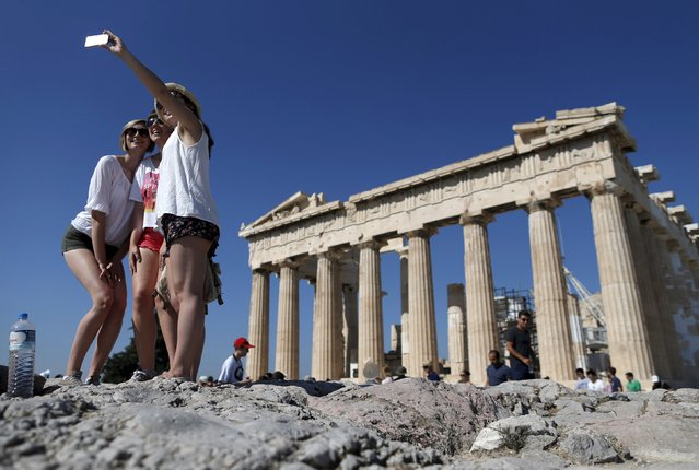 A group of tourists take a selfie in front of the temple of the Parthenon atop the Acropolis in Athens, Greece in this July 9, 2015 file photo. (Photo by Christian Hartmann/Reuters)
