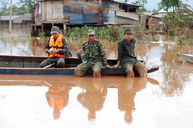 Soldiers sit on a boat during the flood after the Xepian-Xe Nam Noy hydropower dam collapsed in Attapeu province, Laos on July 26, 2018. (Photo by Soe Zeya Tun/Reuters)