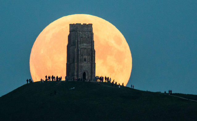 The supermoon rises behind Glastonbury Tor on September 27, 2015 in Glastonbury, England. Tonight's supermoon, so called because it is the closest full moon to the Earth this year, is particularly rare as it coincides with a lunar eclipse, a combination that has not happened since 1982 and won't happen again until 2033. (Photo by Matt Cardy/Getty Images)