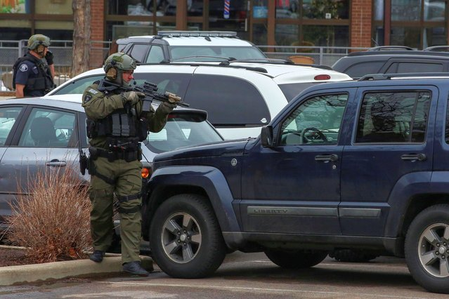 Law enforcement officers sweep the parking lot at the site of a shooting at a King Soopers grocery store in Boulder, Colorado, U.S. March 22, 2021. (Photo by Kevin Mohatt/Reuters)