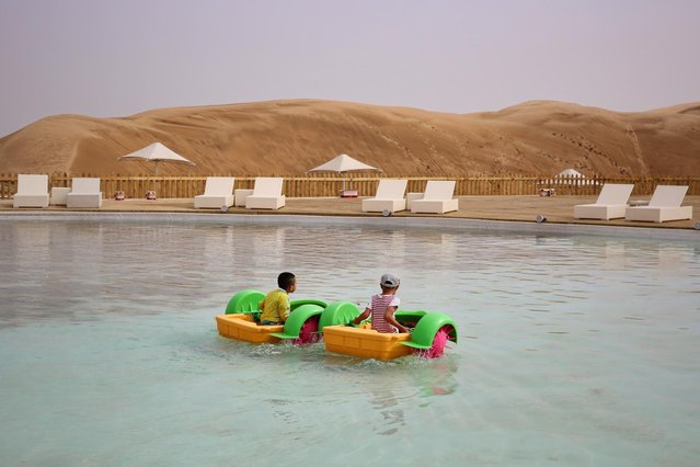 Two lillte boys play in a pool in Xiangshawan Desert, also called Sounding Sand Desert on July 18, 2013 in Ordos of Inner Mongolia Autonomous Region, China. Xiangshawan is China's famous tourist resort in the desert. It is located along the middle section of Kubuqi Desert on the south tip of Dalate League under Ordos City. Sliding down from the 110-metre-high, 45-degree sand hill, running a course of 200 metres, the sands produce the sound of automobile engines, a natural phenomenon that nobody can explain. (Photo by Feng Li/Getty Images)