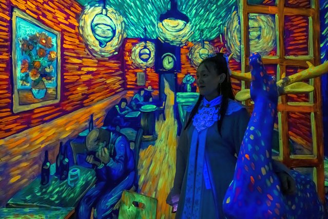 A visitor walks trough an art installation in the Van Gogh Star Art Theme Gallery in Shanghai, China, 30 March 2021. The Van Gogh Star Art Theme Gallery in Shanghai offers visitors a new way to interact with the artwork due to high-technology, special light effects and 4D scenes. The gallery offers appropriate clothing and make-up service for visitors so they can feel blended in the period when Dutch impressionist Vincent Van Gogh was creating while enjoying the art. (Photo by Alex Plavevski/EPA/EFE)