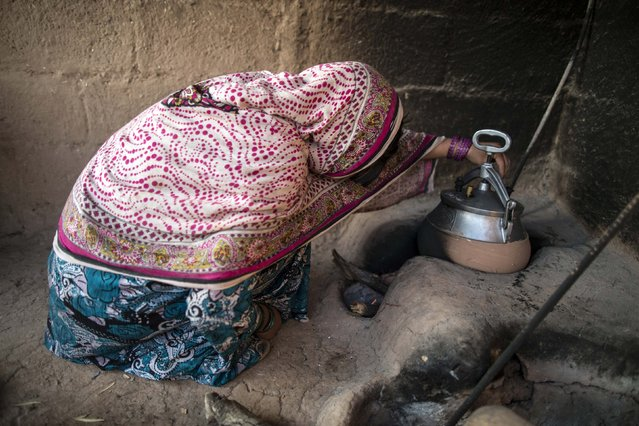 A woman checks her pressure cooker in her house on the outskirts of Islamabad February 11, 2015. (Photo by Zohra Bensemra/Reuters)