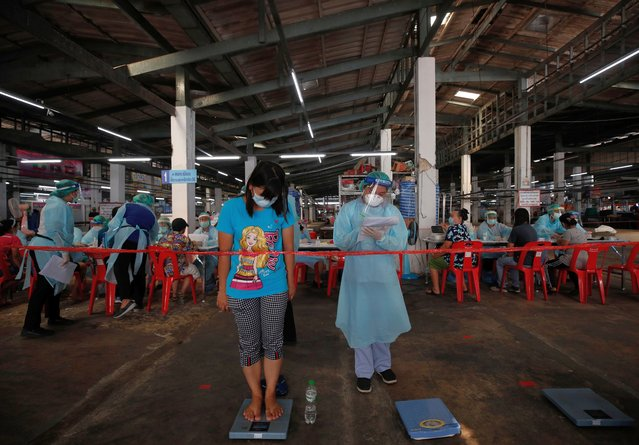 A woman has her weight measured by a medical worker prior to receiving a shot of CoronaVac vaccine against COVID-19, developed by China's Sinovac Biotech, during a mass vaccine inoculation as an effort to curb the spread of a COVID-19 pandemic cluster, at Bang Khae Market in Bangkok, Thailand, 17 March 2021. The Bangkok Metropolitan Administration starts its mass COVID-19 vaccine inoculation for 6,000 people in Bang Khae district to prevent the spread of disease after a new virus cluster was detected that spread hundreds of infections so far. (Photo by Rungroj Yongrit/EPA/EFE)