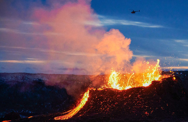 A helicopter flies near above the lava flowing from a fissure near the Fagradalsfjall on the Reykjanes Peninsula in Iceland on ,April 6, 2021. The volcanic eruption, which has been ongoing for more than two weeks in Iceland about 40 kilometers from Reykjavik, spread on April 5, 2021 with a new fault spewing lava, according to the meteorological institute. (Photo by Halldor Kolbeins/AFP Photo)