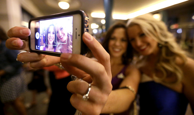 Miss America pageant alumni Miss South Dakota Calista Kirby, left, and Miss Rhode Island Kelsey Fournier take a photograph of themselves with a phone before the Miss America 2014 pageant, Sunday, September 15, 2013, in Atlantic City, N.J. The former misses participated in last year's contest in Las Vegas. (Photo by Julio Cortez/AP Photo)