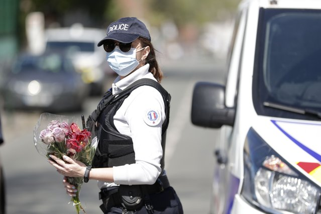 A police officer holds flowers given by residents to be taken down to the police station where a police official was stabbed death Friday in Rambouillet, south west of Paris, Monday, April 26, 2021. Police also called for gatherings at police stations around France after the stabbing in Rambouillet, which authorities are investigating as a terrorist attack. (Photo by Thibault Camus/AP Photo)
