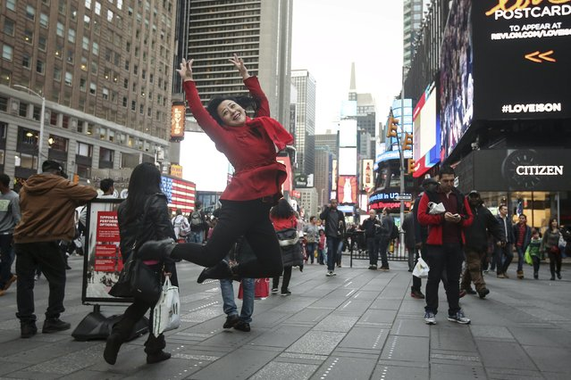A tourist jumps in the air as she poses for a photo in Times Square during unseasonably warm weather on Christmas eve in the Manhattan borough of New York December 24, 2015. (Photo by Carlo Allegri/Reuters)