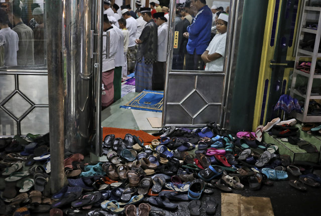 """Footwear are left outside as people perform perform an evening prayer called """"tarawih"""" during the first evening of the holy fasting month of Ramadan, at a mosque in Jakarta, Indonesia, Monday, April 12, 2021. (Photo by Dita Alangkara/AP Photo)"""