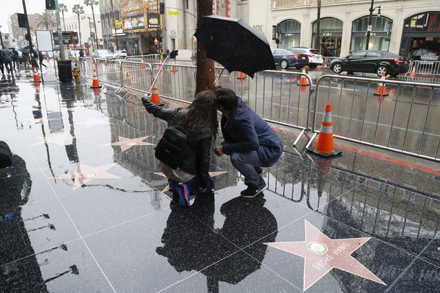Tourists take a selfie in the rain on the Hollywood Walk of Fame in Hollywood, California January 5, 2016. An El Nino-strengthened storm brought widespread rain to drought-stricken California on Tuesday, triggering flooding that clogged roadways, and authorities warned residents about possible mud slides. (Photo by Mario Anzuoni/Reuters)