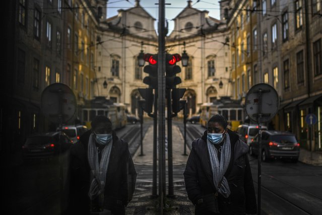 A woman wearing a face mask is reflected in a shop window while walking in Lisbon on January 15, 2021 as Portugal entered a fresh lockdown over a surge in coronavirus cases. The novel coronavirus has killed at least 1,994,833 people since the outbreak emerged in China in December 2019, according to a tally from official sources compiled by AFP. (Photo by Patricia De Melo Moreira/AFP Photo)