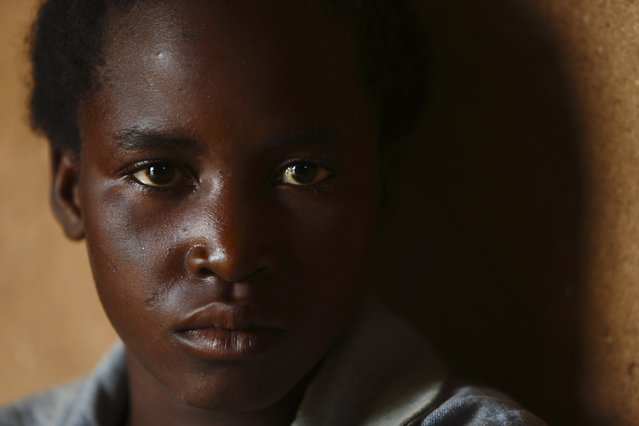 11-year-old Emery Phiri, who was born HIV-positive, attends a self-help group meeting with a caregiver in the village of Michelo, south of the Chikuni Mission in the south of Zambia February 23, 2015. (Photo by Darrin Zammit Lupi/Reuters)
