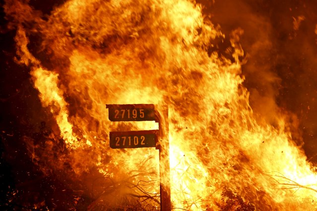 Flames from the Jerusalem Fire consume a sign containing addresses to homes along Morgan Valley Road in Lake County, California in this August 12, 2015 file photo. (Photo by Robert Galbraith/Reuters)