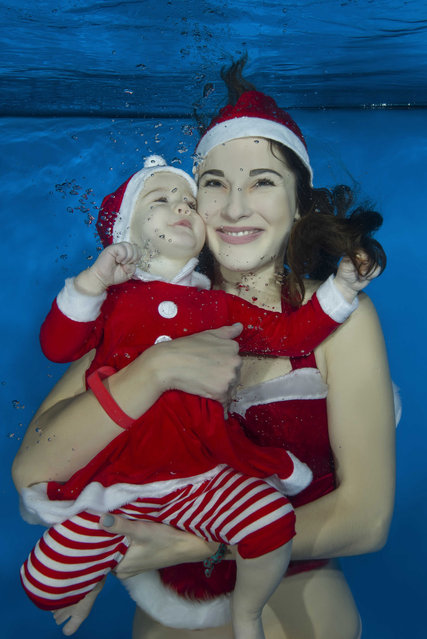 Mama and little girl dressed as Santa floats under water in the pool on December 15, 2016 in Odessa, Ukraine. (Photo by Andrey Nekrasov/Barcroft Images)