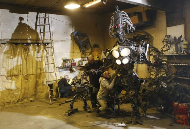 """Mechanic and welder Sergei Kulagin (R), 33, and his collegues work on the """"Alien Aggressor"""", an electro-mechanical robot measuring 3 metres (9 ft.) and approximately 600 kg (1,323 lbs) made by Kulagin with used car components, inside an automobile repair workshop in the Siberian town of Divnogorsk outside Krasnoyarsk, Russia, January 27, 2016. (Photo by Ilya Naymushin/Reuters)"""