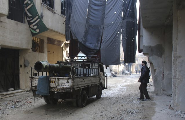 A Free Syrian Army fighter pick-up truck with a locally made weapon installed on it drives under clothes hung for protection against sniper fire in the besieged town of Arbeen in the eastern Ghouta of Damascus January 18, 2015. (Photo by Yaseen Al-Bushy/Reuters)