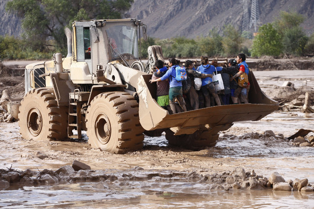 A group of people is transported across a mud covered area on the shovel of a front-end loader after flooding from heavy rains in Copiapo, Chile, Thursday, March 26, 2015. (Photo by Aton Chile/Marcelo Hernandez/AP Photo)