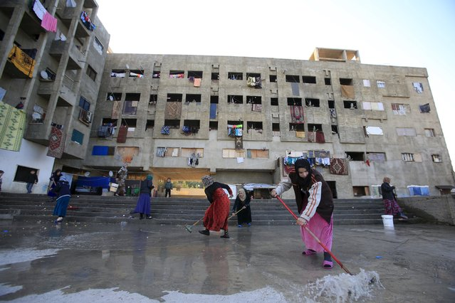 Women clean the floor of a compound housing Syrian refugees in Sidon, southern Lebanon February 3, 2016. (Photo by Ali Hashisho/Reuters)