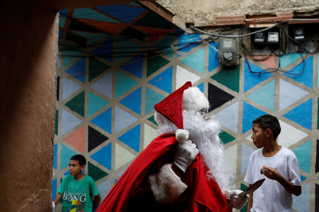 """Richard Gamboa walks in an alley of the slum Cota 905 during the """"Santa en las calles"""" (Santa in the streets) event donating toys, food, and clothes in Caracas, Venezuela on December 1, 2018. (Photo by Marco Bello/Reuters)"""