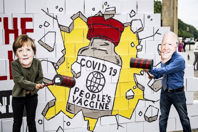 """Activists wearing masks depicting Chancellor Merkel and U.S. President Biden stand in front of a symbolic """"patent wall"""" that they are smashing with hammers in Berlin, Germany, Wednesday, July 14, 20221. The wall reads """"Covid 19 Peoples Vaccine"""". Avaaz activists are calling for the temporary suspension of patent protection for Covid vaccines. (Photo by Fabian Sommer/dpa via AP Photo)"""