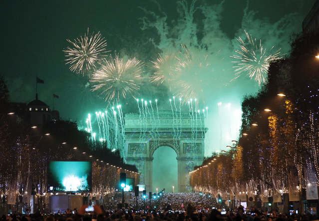 Revellers photograph fireworks over the Arc de Triomphe as they celebrate the New Year on the Champs Elysees, in Paris, France, Sunday, January 1, 2017. (Photo by Christophe Ena/AP Photo)